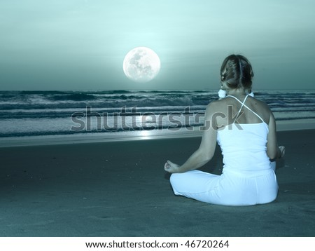 Woman is meditating at twilight time under moon - stock photo