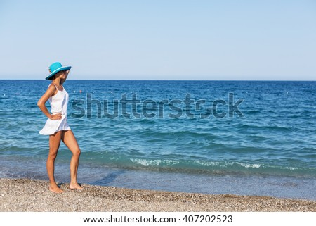Woman is on the beach near the edge of water. - stock photo