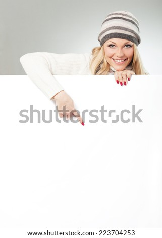 Woman is pointing with her finger on a large copy space - stock photo