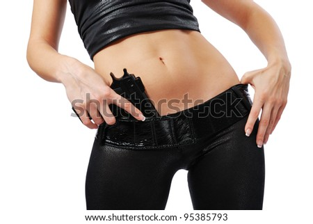 Woman is pushing a handgun into her skintight pants. She is wearing a black leather top and trousers. Her both arms and a middle part of her sexy body are in sight. - stock photo