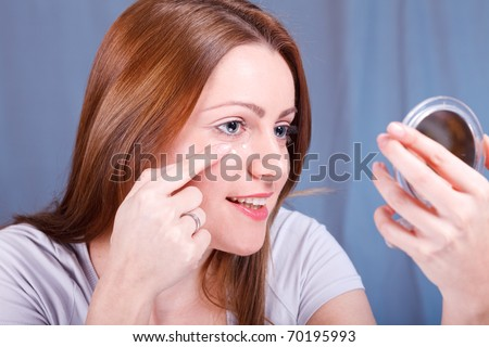 Woman is putting Anti-Wrinkle cream on face - stock photo