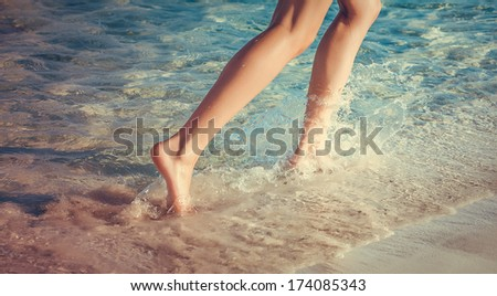 Woman is running ahead on beach of sea. Legs close-up - stock photo