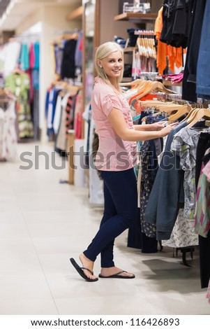 Woman is searching for clothes smiling - stock photo