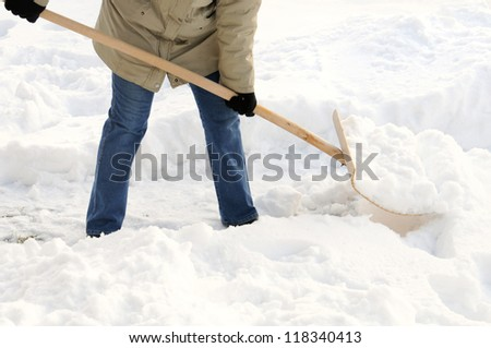 Woman is shovelling snow - stock photo