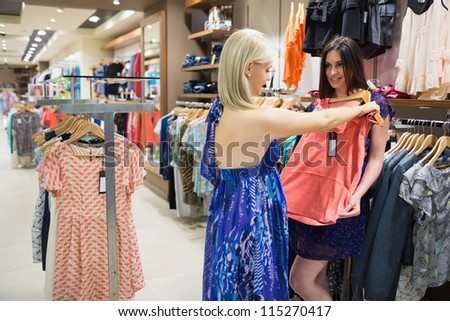 Woman is showing orange shirt to friend in shopping mall - stock photo
