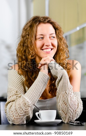 woman is sitting at cafe and smiling - stock photo