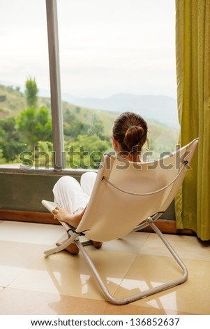 Woman is sitting in cozy armchair at hotel high up in mountains of Sri Lanka - stock photo