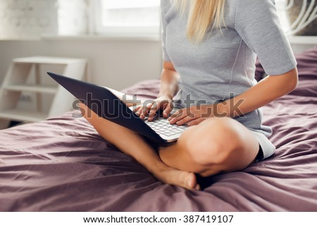 Woman is sitting on bed with a laptop - stock photo