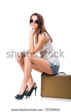 woman is sitting on old leather case - stock photo