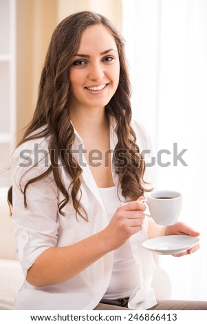 Woman is sitting on the couch with a cup in her hands and smiling. - stock photo