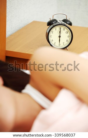 Woman is sleeping, alarm clock on table. In home. - stock photo