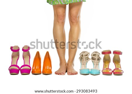 Woman is standing barefoot in between a group of fashionable high heels shoes. - stock photo