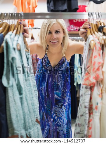 Woman is standing between a clothes stand watching and smiling - stock photo