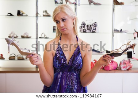 Woman is standing in front of a shelf choosing shoes - stock photo