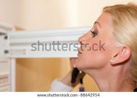 Woman is standing in front of her letter box and is looking after her mail - stock photo
