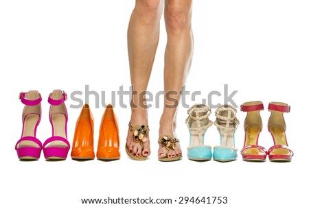 Woman is standing in slippers in between high heels shoes - stock photo