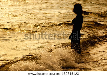 Woman is standing near the sea. Sunset - stock photo