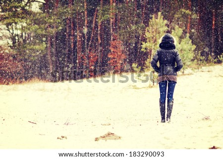 Woman is standing on meadow in the forest durring wintertime. - stock photo