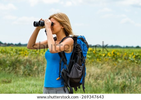 Woman is standing on the country road and watching something through binoculars .Enjoying in nature with binoculars - stock photo
