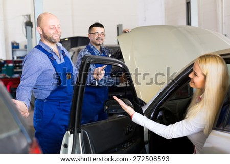 Woman is taking her car to mechanics for service - stock photo