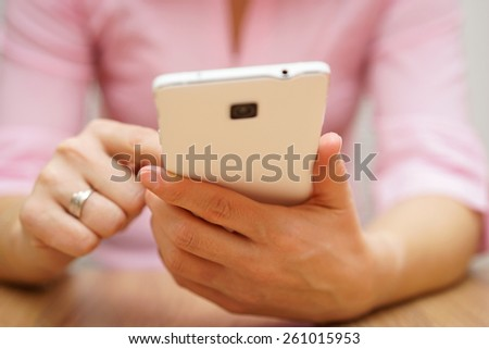 woman is typing on touch screen on mobile phone - stock photo
