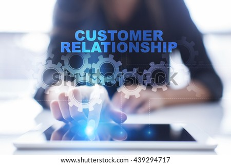 """Woman is using tablet pc, pressing on virtual screen and select """"Customer Relationship"""".  - stock photo"""