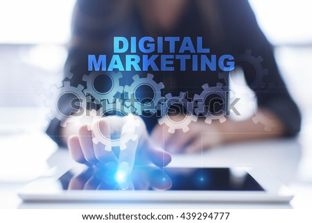 """Woman is using tablet pc, pressing on virtual screen and select """"Digital Marketing"""".  - stock photo"""