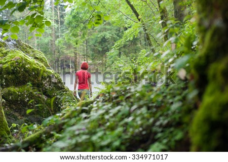 Woman is walking away to the beautiful, mysterious and green wood with red t-shirt  - stock photo