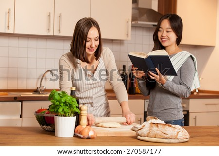 Woman is working on a dough while her friend is reading a cookbook - stock photo