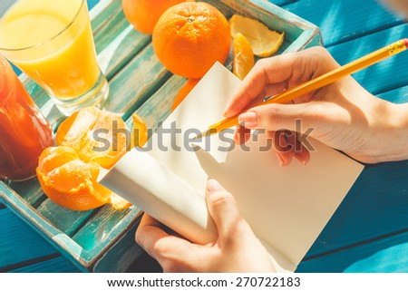 Woman is writing in her notebook in the sunny morning. - stock photo