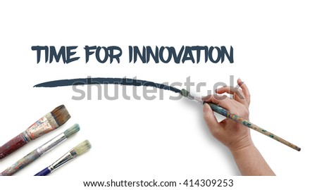 Woman is writing TIME FOR INNOVATION with paintbrush. - stock photo