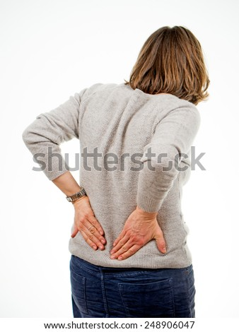 Woman isolated on white background holds her back - stock photo