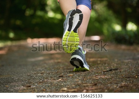 Woman jogging away from camera wearing trainers - stock photo