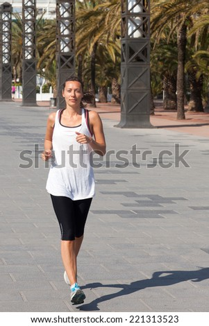 Woman jogging in summer under palm trees - stock photo
