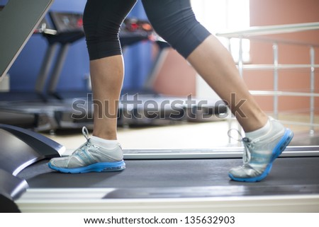 Woman jogging on exercise treadmill in local gym. - stock photo