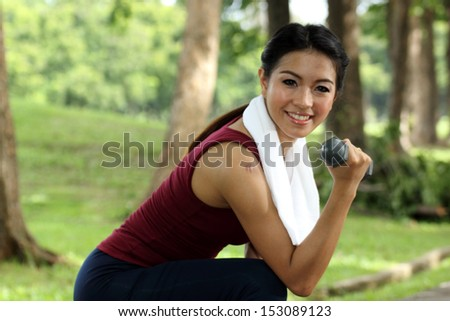 woman jogging on running trail with hand weights - stock photo