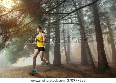 Woman jogging. Young girl running in the woods. Runner athlete in the forest. - stock photo