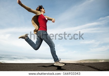 Woman jumping against a blue sky - stock photo
