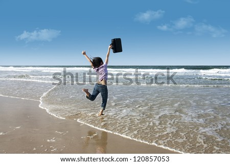Woman jumping excitedly at the beach while holding her laptop - stock photo