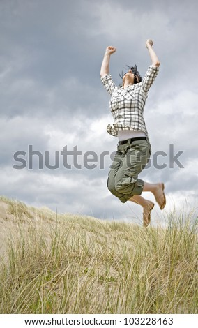 woman jumping for joy in sand dunes - stock photo