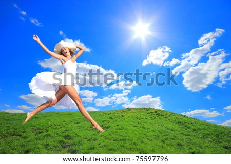 Woman  Jumping for Joy on a Grass Hill - stock photo