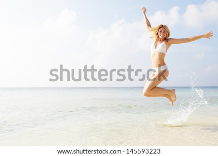 Woman Jumping In The Air On Tropical Beach - stock photo