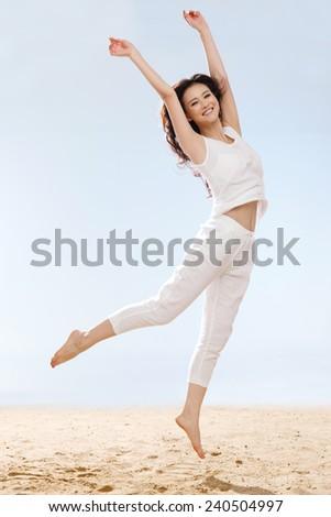 Woman jumping on beach - stock photo