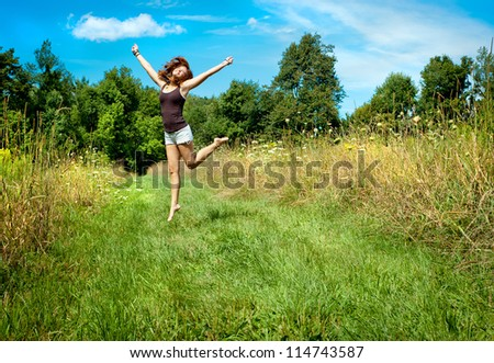 Woman jumping on nature walkway - stock photo