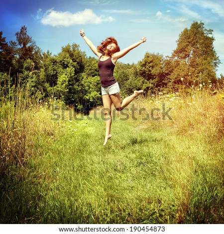 Woman jumping on nature walkway, instagram filter style - stock photo