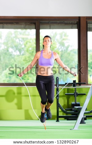 Woman jumping with rope, jumping rope in a fitness club or gym - stock photo