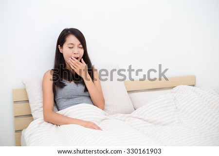 Woman just wake up and sitting on bed - stock photo