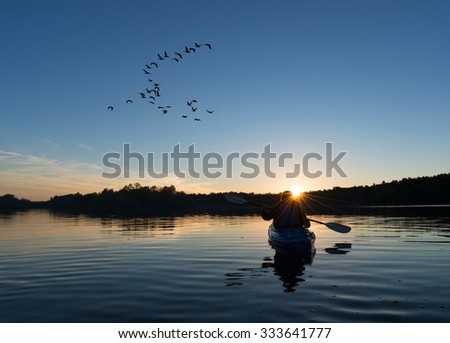Woman kayaking at sunset with a flock of geese looking to land on the northern lake - stock photo