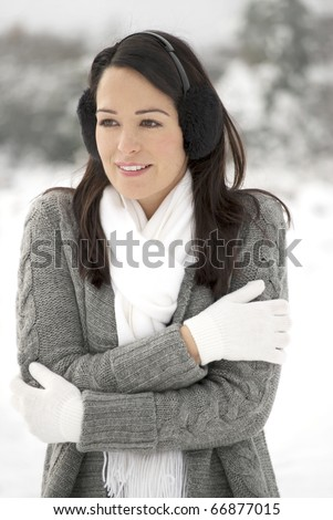 Woman keeping warm outside in the snow - stock photo