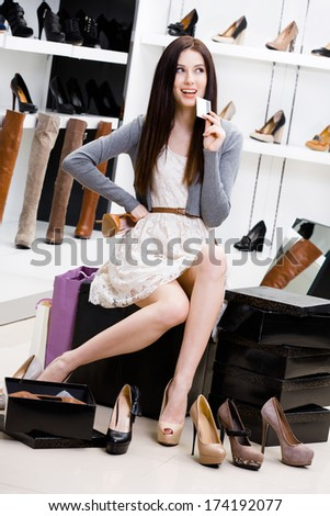 Woman keeps credit card in footwear shop sitting on the chair and trying on different pairs of pumps - stock photo